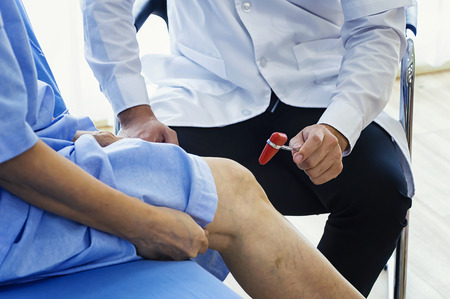 Photo pour Close-up of female physiotherapist massaging the leg of patient in a physio room. Man doctor checking with sensory hammer. - image libre de droit