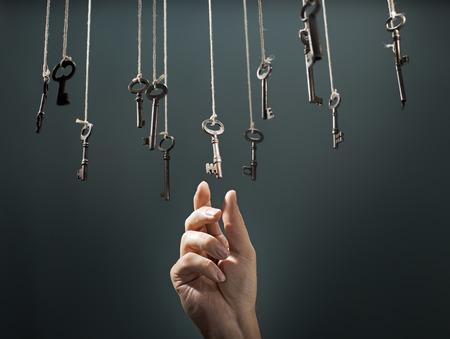 Photo pour Hand choosing a hanging key amongst other ones. - image libre de droit