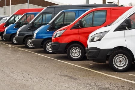 Photo pour row of different marques of commercial vehicles or vans for retail sale on a motor dealers lot all logos removed - image libre de droit