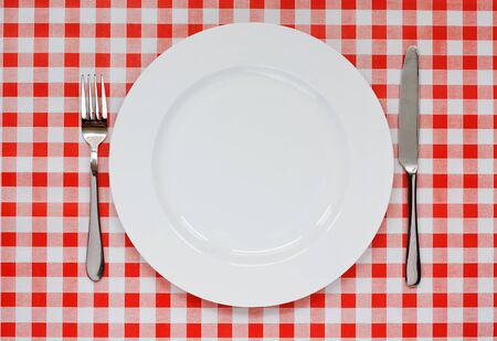 Empty plate setting with plate, knife and fork on red gingham background popular symbol for diners and cafes