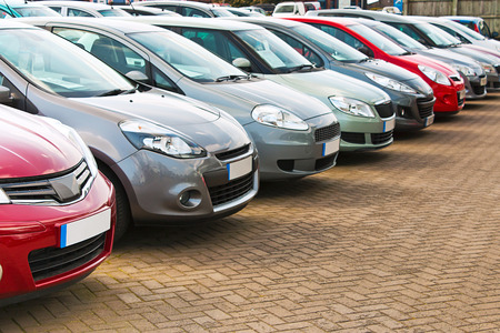 Photo pour Line up of various types of used cars for sale on a motor dealers forecourt all marques removed - image libre de droit