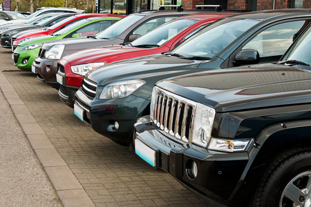 Photo pour Row of used four by four motorcars also known as 4x4, SUV, off road, utility vehicle, ute or Station wagon arranged for sale on a motor dealers forecourt these types are becoming popular choices to buy as a new family car with off road capability but just - image libre de droit