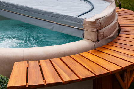 Photo pour The ultimate garden accessory a free standing cedar wood and leather circular hot tub with cover. - image libre de droit