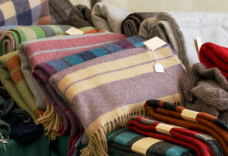 Foto de Selection of throws traditionally made of wool in a pile for sale at market traders, great example of crafting industry. - Imagen libre de derechos