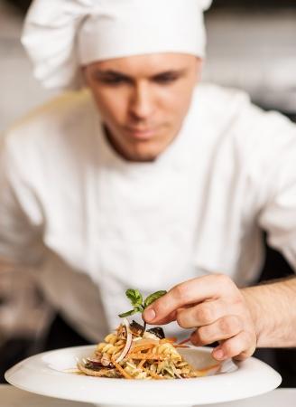Foto de Handsome male chef dressed in white uniform decorating pasta salad - Imagen libre de derechos