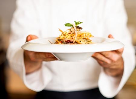 Foto de Chef holding mouth watering pasta salad, ready to serve. - Imagen libre de derechos
