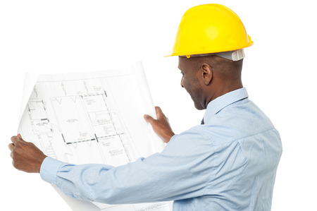 Photo for Construction engineer with hardhat reviewing building plan - Royalty Free Image