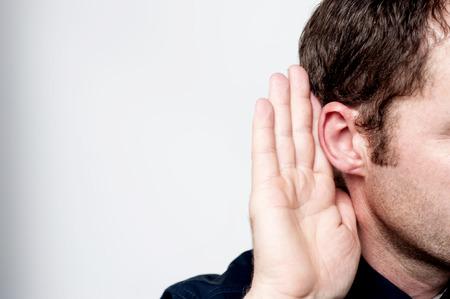 Foto de Listening male holds his hand near his ear - Imagen libre de derechos