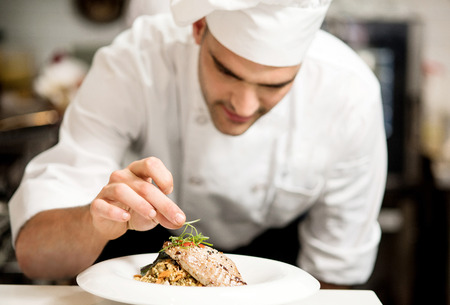 Foto de Male chef garnishing his dish, ready to serve - Imagen libre de derechos