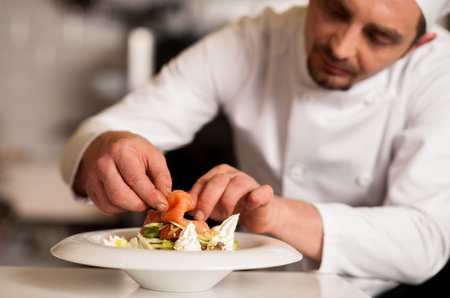 Photo for Chef adding topping for smoked salmon salad - Royalty Free Image