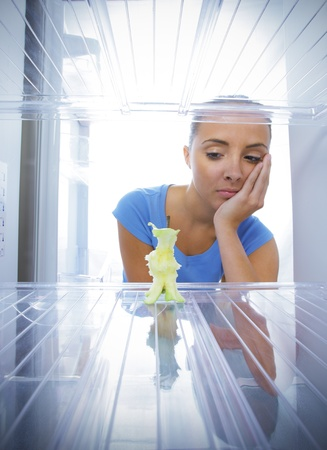 Young woman unhappy to see the empty fridge