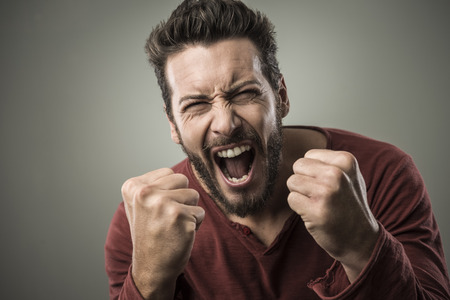 Angry aggressive man shouting out loud with ferocious expression