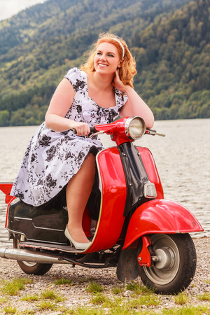 Red-haired beauty with overweight on a red motor scooter at sea