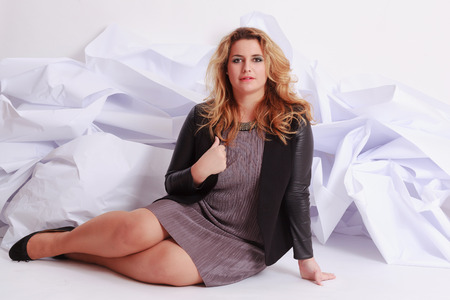 Fashionable, elegant woman with voluptuous curves in a gray dress, sitting in front of a white paper studio shot.