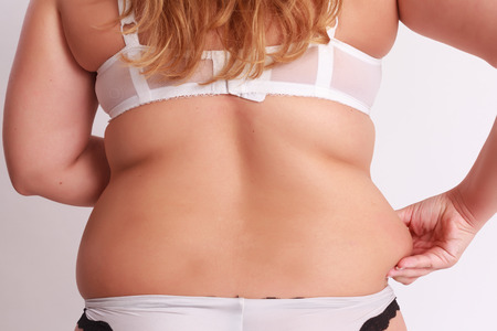 Photo pour Woman pinches in the fat at the waist with back to camera. - image libre de droit