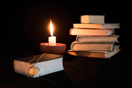 Foto de Still life on black background with stacked books, candle and single book on foreground on which lays 40 years old golden clock with a chain. Text on watch says Chaika, 17 stones, made in USSR. - Imagen libre de derechos