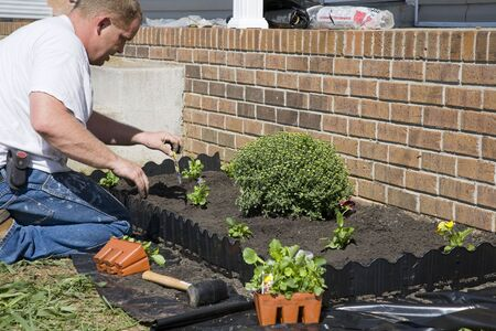 Man planting flowers in garden, dressing up landscape to help sell home