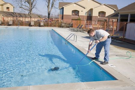 Service man cleaning pool filters, removing leaves that have fallen in pool this fall