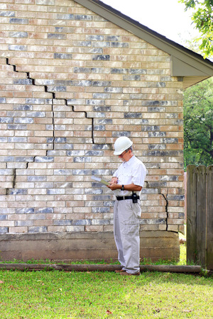Foto de Inspector inspecting home?s foundation is experiencing settlement (collapse). Eventually the brick veneer begins to separate from door and window frames. Finally framing and roof problems occur, as well as plumbing problems. Foundation problems don?t get  - Imagen libre de derechos