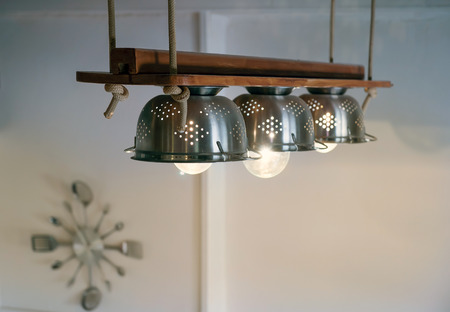 Photo for Warm lighting coming out from beautiful diy with kitchen equipment, lamps,ropes and wood hanged  from the ceiling - Royalty Free Image