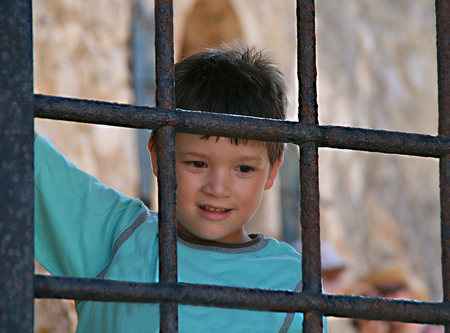 Happy boy standing and looking  behind an old iron gate on greek castle