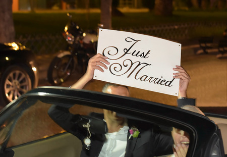 Photo for A newlywed couple is driving a convertible modern car on a road for their honeymoon. The bride is driving and the husband holding a just married placard, front view - Royalty Free Image