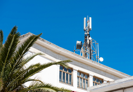Photo pour Cell phone telecommunications antennas and repeaters on building against clear blue sky - image libre de droit