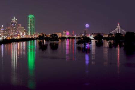 Photo pour Long exposure photo of the lights of the Dallas Texas skyline reflecting on the flooded Trinity River with trees in the river silhouetted by the glowing reflection. - image libre de droit