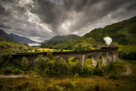Foto de Jacobite steam train on old viaduct in Glenfinnan with mountains and Loch Shiel in background, Scotland - Imagen libre de derechos
