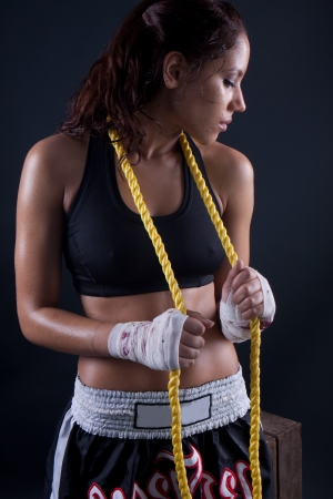 Beautiful fitness body passion for exercising. wet brunette holding a rope