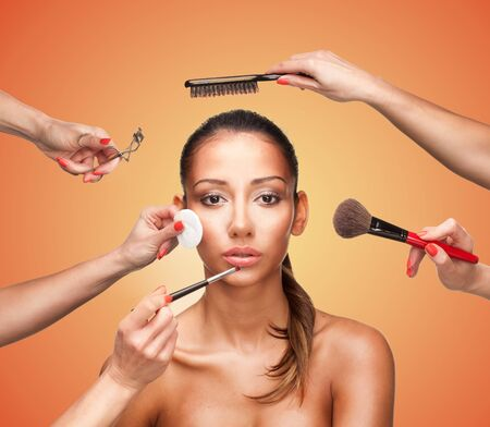 Photo pour Conceptual beauty and fashion image of the hands of several beauticians and stylists holding their respective equipment giving a glamour makeover to a beautiful woman - image libre de droit