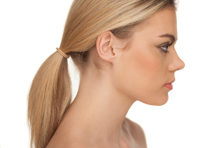Foto de Close-up profile portrait of a beautiful blond woman with serious expression and looking down on a white background - Imagen libre de derechos