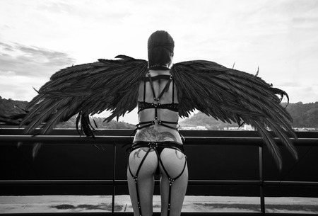 Photo for Back view black and white photo of beautiful seductive angel woman with covered eyes wearing lingerie and leather belts standing on the roof over cloudy sky - Royalty Free Image