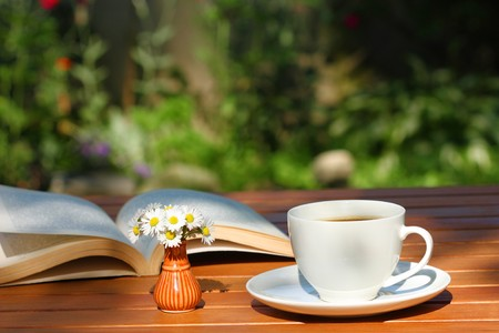 Foto de Coffee and book on the garden table - Imagen libre de derechos