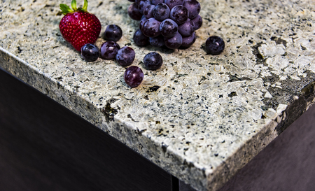 Foto de Stone table top (as kitchen island) on blur kitchen background floor - can be used for display or montage your products - Imagen libre de derechos