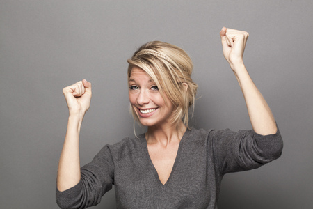 success concept - happy young blonde woman winning a competition with fun body language and hands up