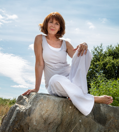 Photo pour senior zen - smiling, beautifully aging woman sitting on a stone for outdoors yoga session wearing white seeking serenity and wellness in a park,summer daylight - image libre de droit