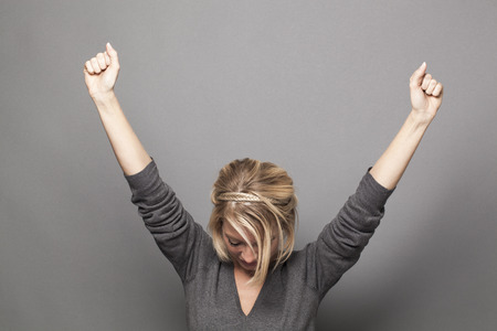 Photo for success concept - successful young blonde woman winning a competition with both hands raised up above with head down for thanks and humility - Royalty Free Image