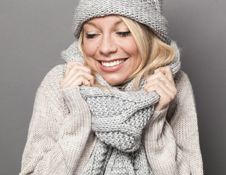 trendy warm winter - gorgeous young blond woman wrapping up herself in gray wool winter hat and scarf smiling for softness and cozy fashion
