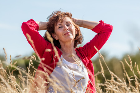 Foto per female casual relaxation - smiling radiant mature woman enjoying fresh air in her hair,being in harmony with nature in long summer grass field seeking for peace,summer daylight - Immagine Royalty Free