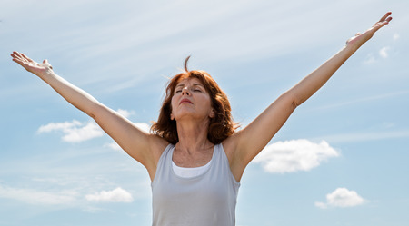 Foto per senior zen - thinking beautiful mature woman opening her chakra and arms wide,seeking for harmony and wellbeing outdoors in summer daylight - Immagine Royalty Free