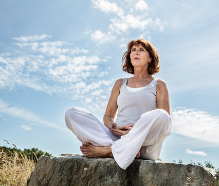 Foto per breathing outdoors - beautiful middle aged woman sitting on a stone in yoga lotus position, wearing white, seeking for balance over summer blue sky,low angle view - Immagine Royalty Free