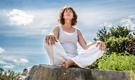 Photo for exercising outside - radiant 50s yoga woman sitting on a stone, seeking for spiritual balance with tree background,low angle view - Royalty Free Image