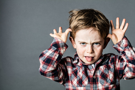 Foto de angry little brat enjoying making a grimace, sticking out his tongue, playing with his hands for  misbehavior, contrast effects, grey background - Imagen libre de derechos