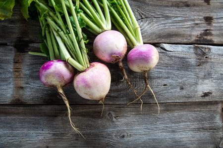 Foto de rustic organic turnips with fresh green tops and roots on genuine wood background for sustainable agriculture and vegetarian food, flat lay - Imagen libre de derechos