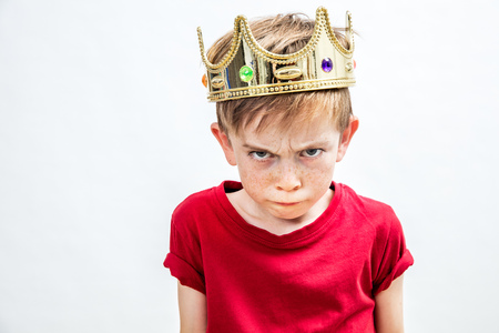 Photo pour irritated beautiful spoiled boy with frowning freckles and a dirty look wearing a golden crown for mad attitude facing parenthood and education, white background, indoors - image libre de droit