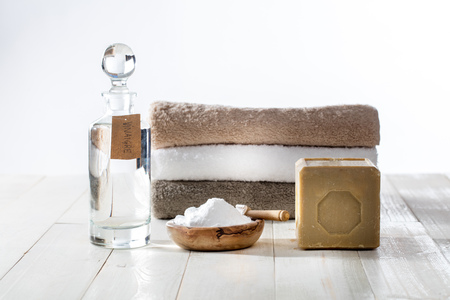 Foto de Sustainable cleaning laundry with chic homemade detergents and softener with traditional Marseilles soap, vinegar and baking soda for fluffy folded towels on wooden background - Imagen libre de derechos
