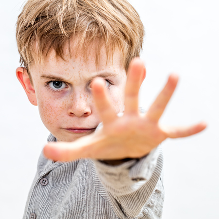 Photo pour scared 6-year old little child with hand forwards defending himself, stopping violence or abuse at school, or acting like a bully or brat threatening preschooler, white background - image libre de droit