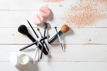 Photo pour Concept of cosmetics and makeup with free powder, skincare and various professional make up face brushes over white wooden background for elegant beauty background, flat lay view - image libre de droit