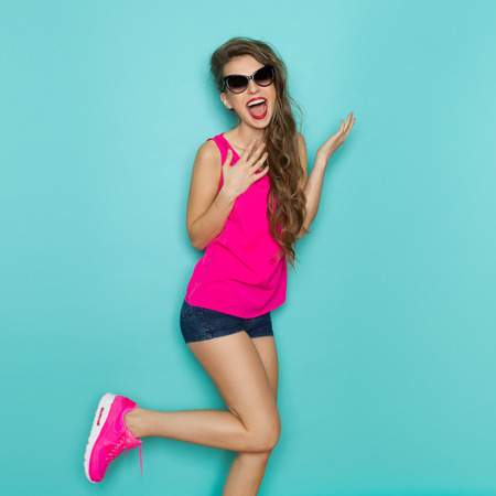Photo pour Shouting young woman in sunglasses, pink shirt, jeans shorts, and pink sneakers posing on one leg. Three quarter length studio shot on a teal background. - image libre de droit